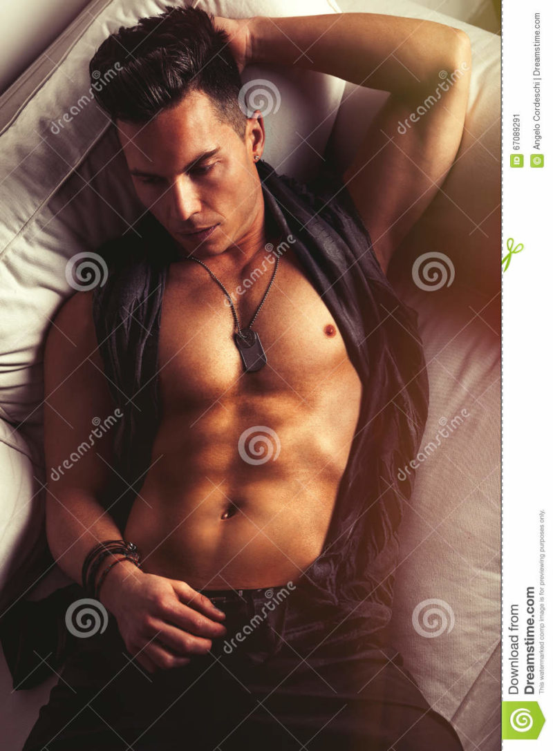 Attractive sexy male, handsome cool man A beautiful stylish man in glamorous style. Chest discovered with metal necklace. Stylish hair. Relaxed lying on the white sofa.
