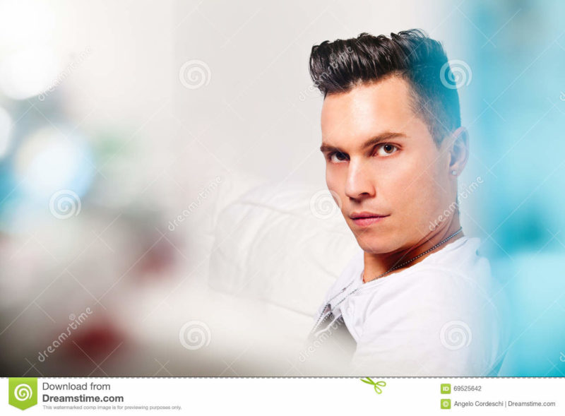Beautiful model, handsome man portrait. Hairstyle modern look Close portrait of a young man with stylish hair. Lights, colors, bokeh. Beautiful face and serene expression. Intense look.