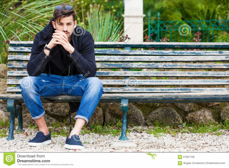 Boyfriend waiting. Handsome young man model sitting on the bench A handsome young man is sitting on a bench watching and waiting. The boy wearing trendy clothes. Beside him the empty bench. Waiting for someone or simply rest. Location: Rome, Italy. Park in the city center.