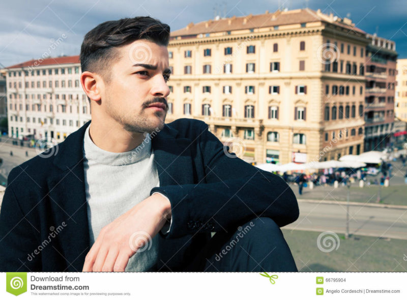 City handsome man, fashion modern hair A handsome boy looking, stylish hair and modern clothes. Horizontal portrait behind him some historic buildings in Rome, Italy. Urban scene.