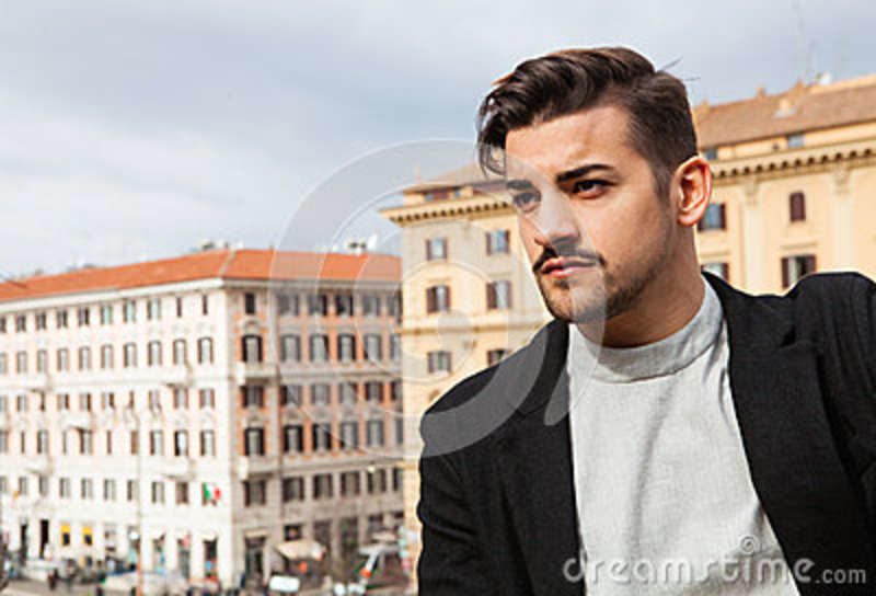 City handsome man, fashion modern hair A handsome boy looking, stylish hair and modern clothes. Horizontal portrait behind him two historic buildings in Rome, Italy. Urban scene.