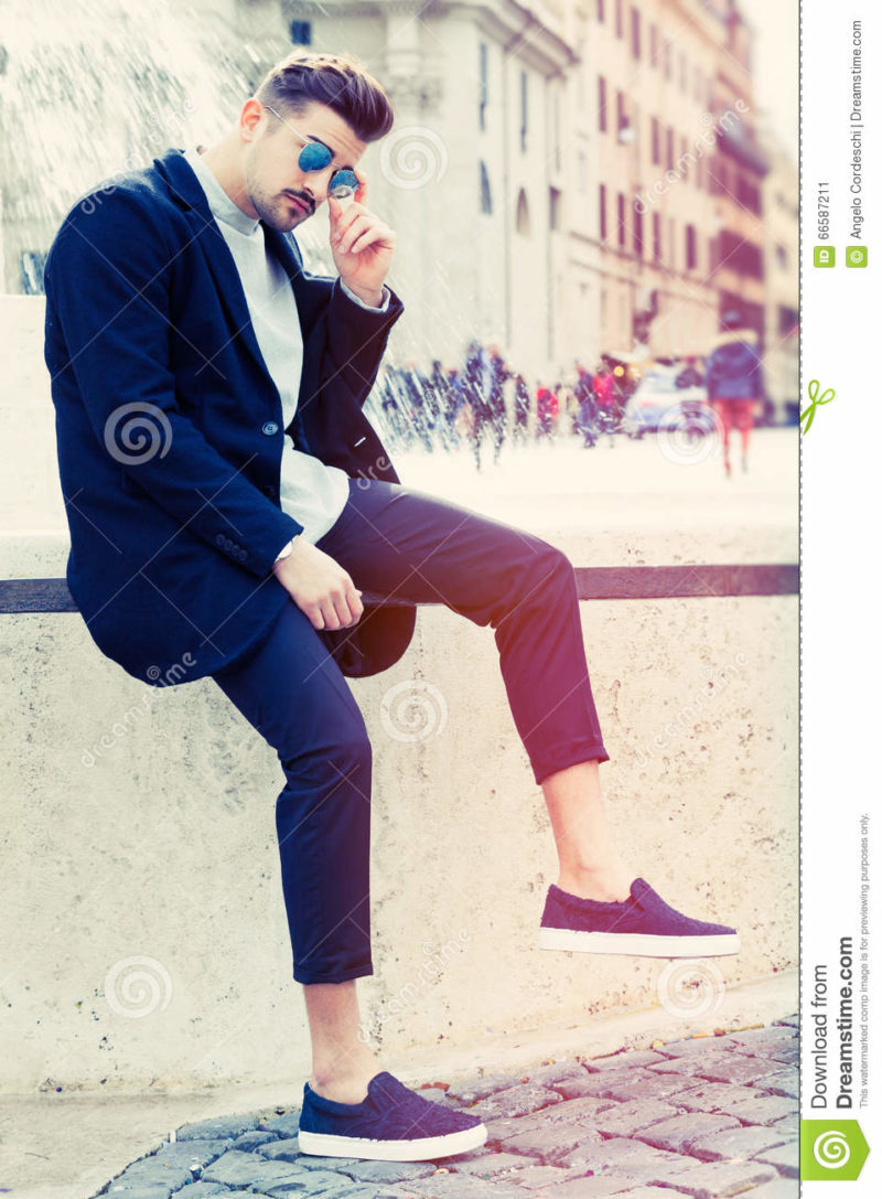 Cool handsome fashion young man. Stylish man in the city A charming young stylish man with sunglasses. Sitting position, confident attitude with setting in the historic city of Rome, Italy. Fashionable clothes.