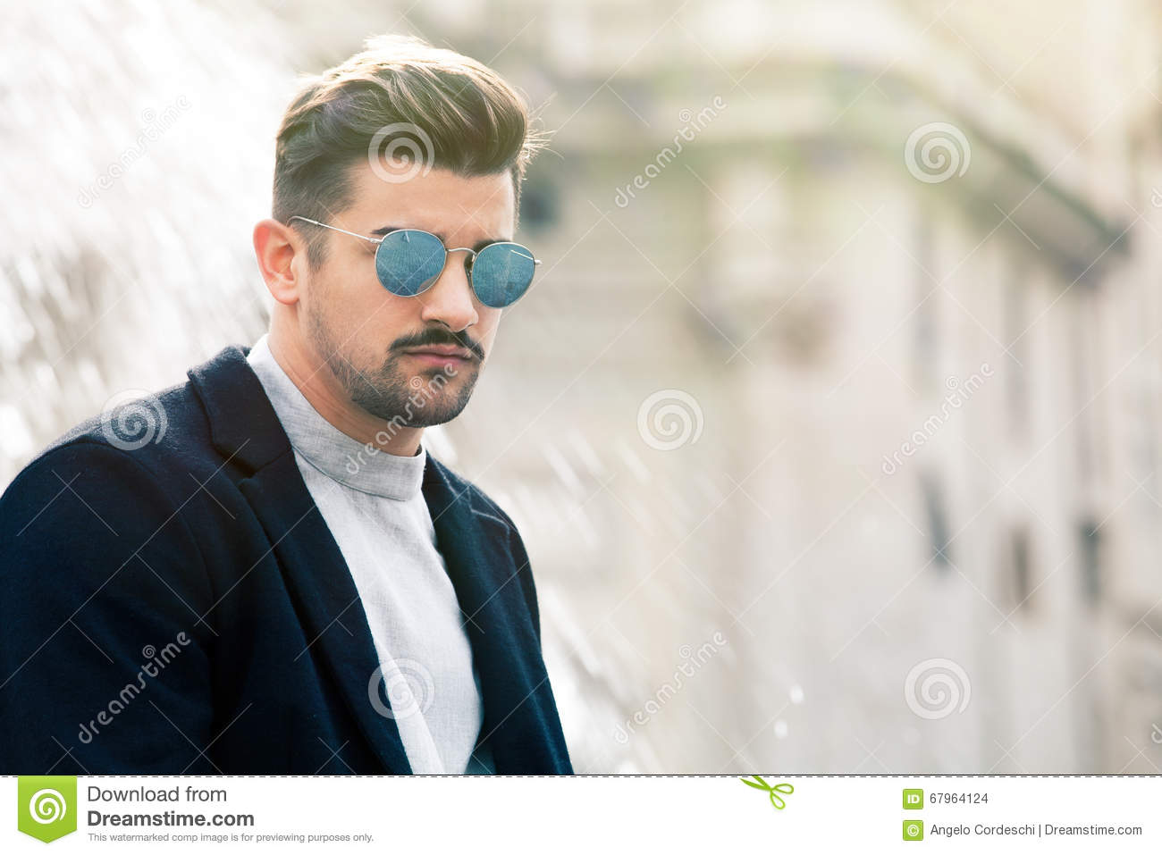 Cool handsome fashion young man. Stylish man with sunglasses A charming young stylish man with sunglasses. Confident attitude with setting in the historic city of Rome, Italy. Fashionable clothes.