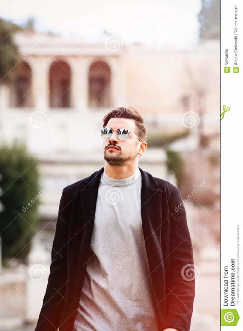 Cool handsome fashion young man. Stylish man with sunglasses A young and handsome man with sunglasses is walking in the city looking up. Trendy and modern clothing concept. The beautiful boy has a slight beard, gray shirt and black jacket. Behind him, the ancient city of Rome with blurred construction. Italy.
