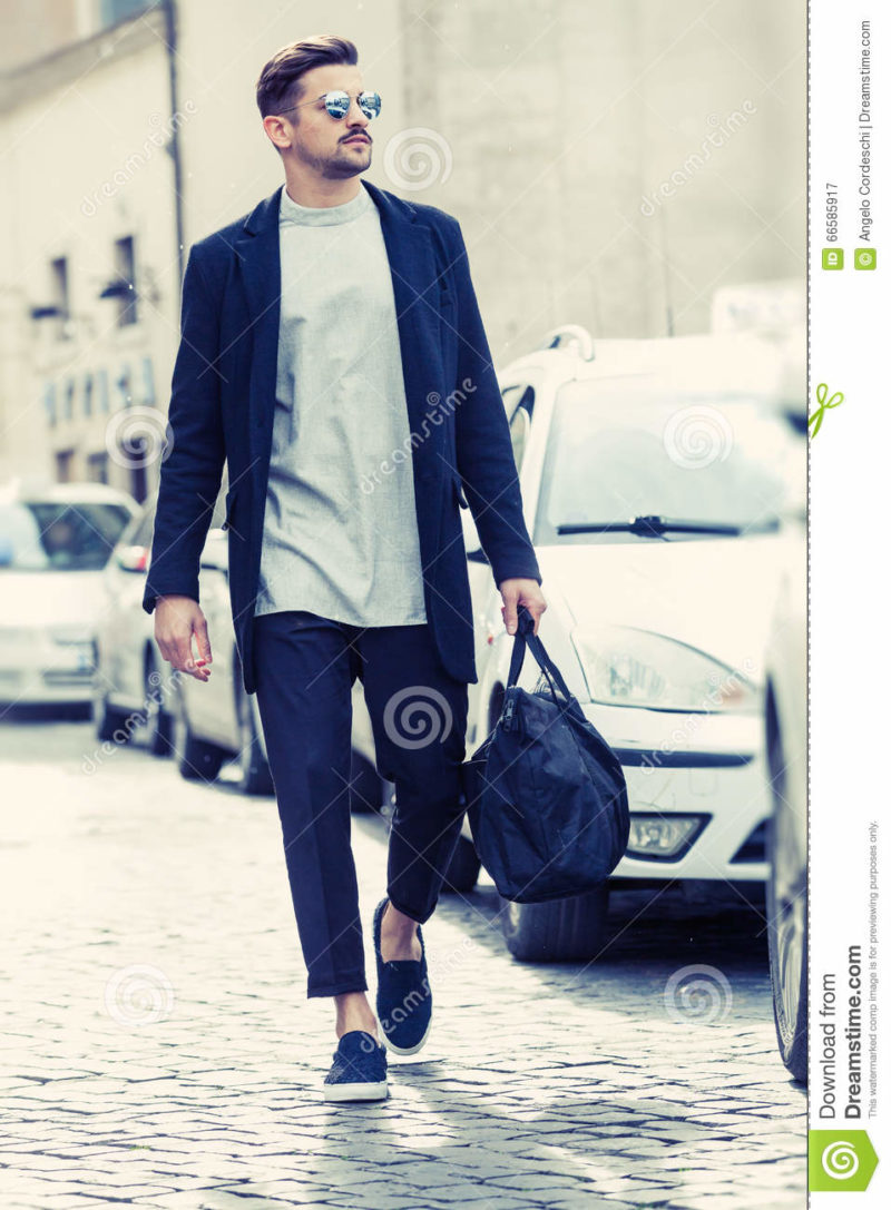 Cool man beautiful model outdoors, city style fashion A handsome man model walking in the city center next to some cars. urban setting. The young boy as trendy, modern clothing with bag. Cobblestones to the ground.