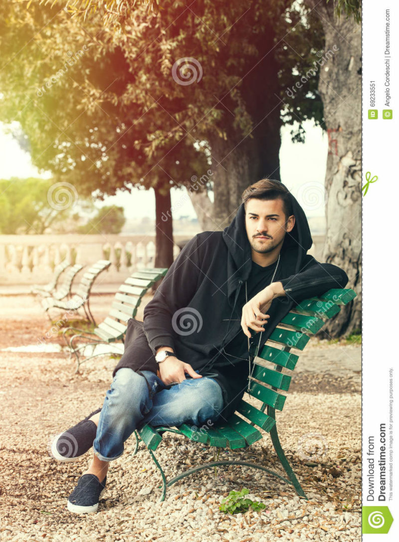 Fashionable cool young man relaxing on a bench in a park with trees A young handsome man sitting on a bench in the historic center of Rome, Italy. The boy dresses fashionable, wearing partially a hoodie. Outdoors in a park.