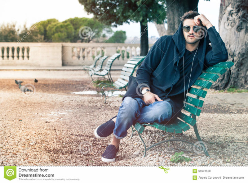 Fashionable cool young man with sunglasses relaxing on a bench A young handsome man sitting on a bench in the historic center of Rome, Italy. The boy dresses fashionable, wearing sunglasses and hoodie. Outdoors in a park.
