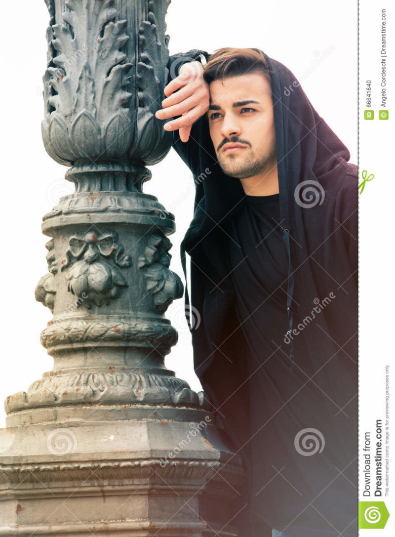 Gorgeous young man leaning against a old lamppost A handsome young man with hoodie is in the historic center of Rome, Italy. The boy is leaning against a pole of a streetlight. clean and youthful face. Beard. white background.