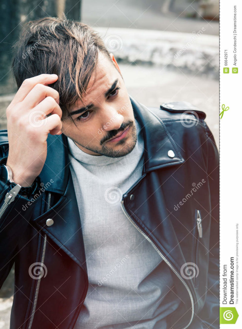 Hairstyle young man outdoors. Hair male A young and handsome guy is outdoors. He is touching the straight brown hair. Charming and youthful look. Leather jacket and light beard.