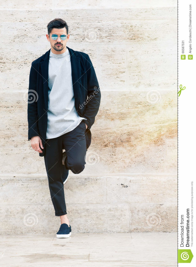 Handsome fashionable man, white wall A handsome young man with stylish sunglasses and fashionable clothes leaning against a marble wall white. Copyspace to the right