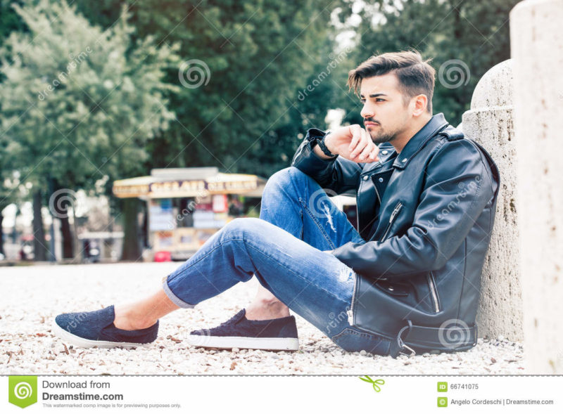 Handsome gorgeous young man model outdoors A handsome and charming boy is sitting on the ground waiting. The young man has a beautiful face and stylish hair, he wears casual jeans and leather jacket, trousers with cuffs, rolled up pants. Outdoors in a park in Rome, Italy.