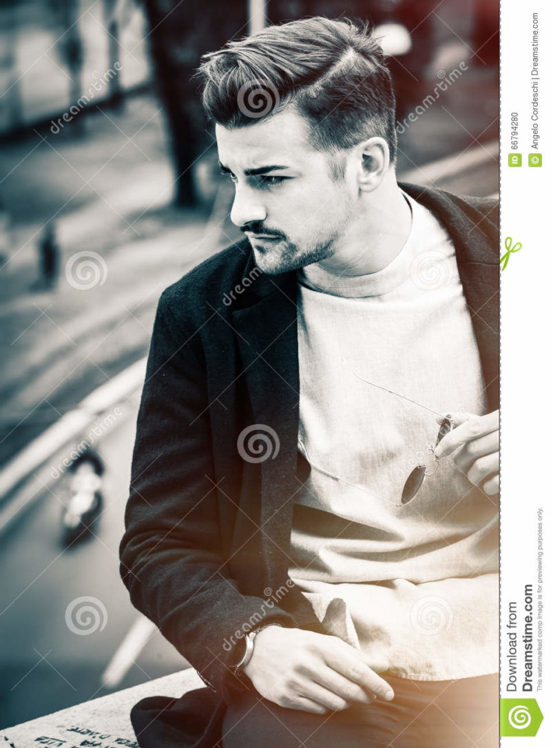 Handsome hairstyle young man city outdoors. Black and white Outdoor portrait of a handsome young man. Sunglasses in hand and stylish hair. Behind him a city street. Youth fashion. Black and white