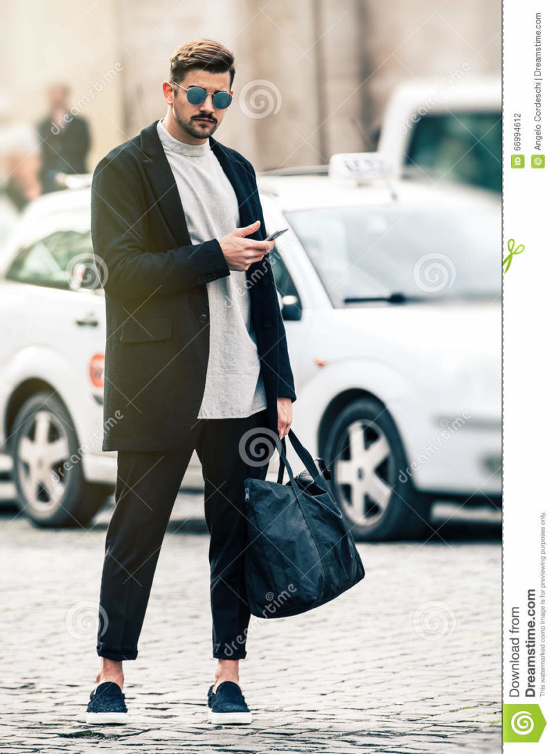 Handsome man model with sunglasses and cell phone outdoors A young and handsome man model is with mobile phone in hand, standing outdoors with urban traffic behind. The boy dresses fashionable, wearing sunglasses, trousers with a flap, a black bag in his hand. In the historic center of Rome, Italy.