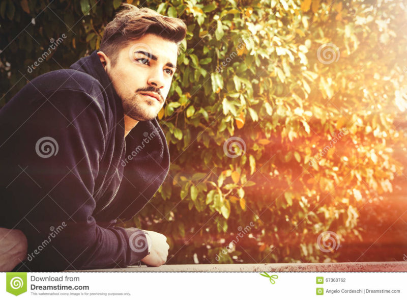 Handsome young harmony italian man - Romantic waiting A handsome young man leaning on a wall waiting for in a park with trees and leaves in the background. The young boy has a slight beard. He is wearing a coat.