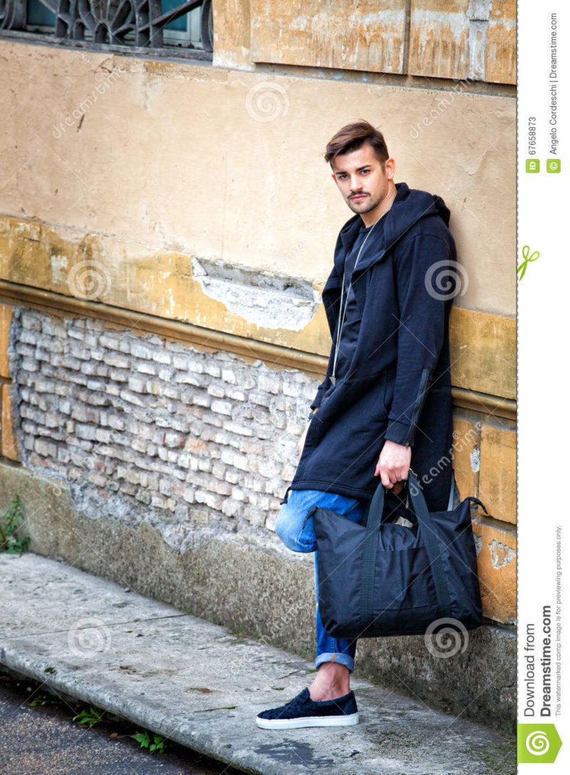 Handsome young man model on the go. Street wall Handsome young man model on the go. On the street leaning against the wall. A beautiful model with a black bag is waiting leaning against an ancient wall of an old building.