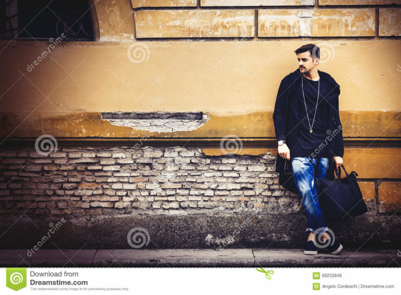 Handsome young man model on street grunge wall Handsome young man model on the go. On the street leaning against the wall. A beautiful model with a black bag is waiting leaning against an ancient wall of an old building.