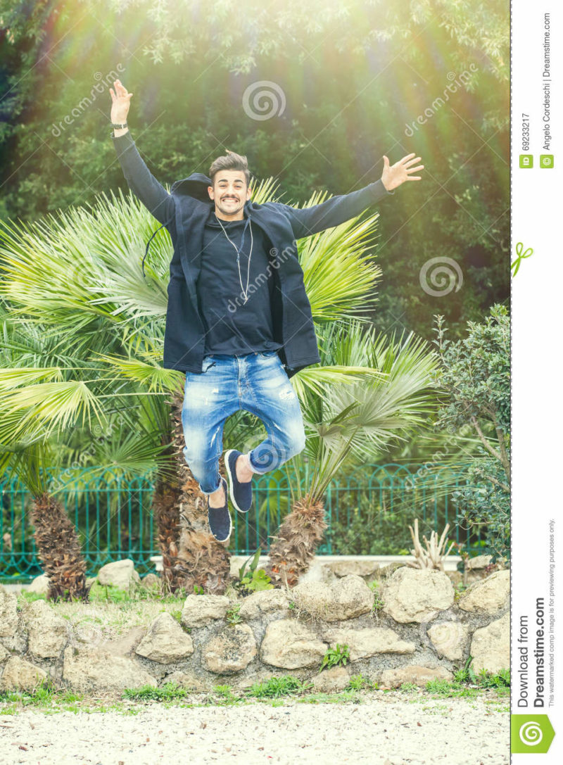 Happiness success of a young man outdoors. Jumping for joy A young and handsome man is jumping with joy, happiness and joy outdoor in a park. Smiling, with a modern look and stylish. Bright daylight.