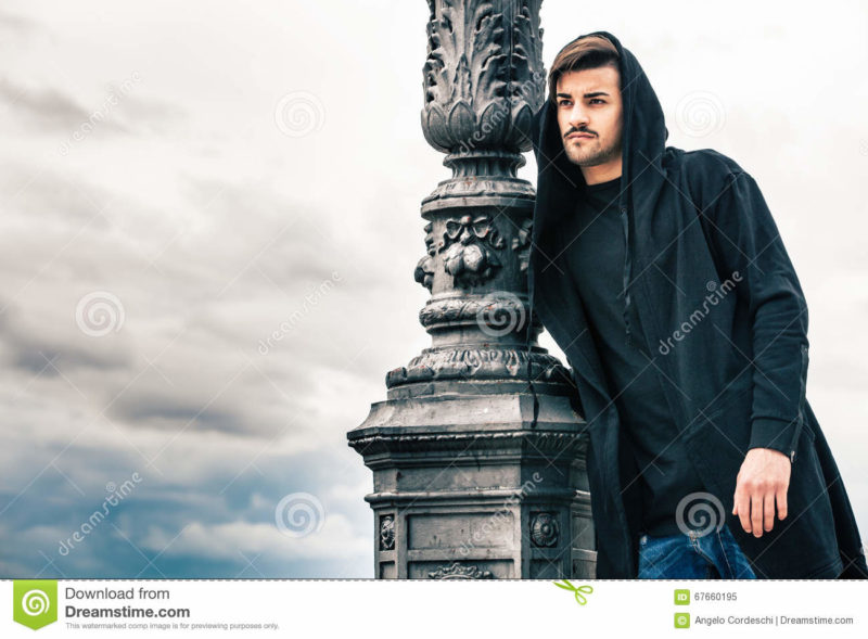 Mysterious and handsome young man model with hoody. Cloudy sky A glamorous young man is leaning against a lamppost standing outdoors. The boy is wearing a dark sweatshirt with a hood on his head. The pole is made of iron and has numerous decorations. Behind him the sky covered by clouds. Location: Rome, Italy