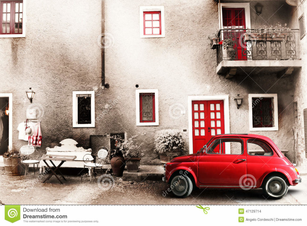 Old vintage italian scene. Small antique red car. Aging effect An old Italian with out a small subcompact old car. Vintage scene. Two chairs, a bench and a small table outside the home. A balcony with flowers and other objects of another era. Doors and windows red.