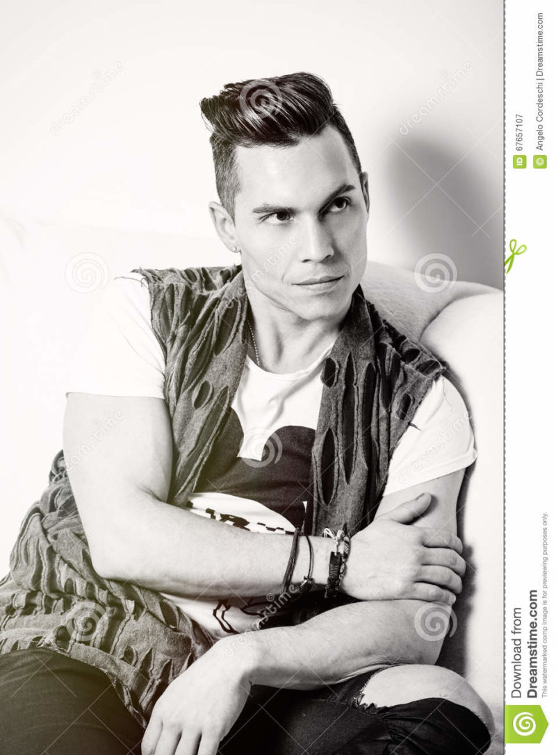 Portrait handsome man, stylish hair cut. Black and white A handsome young Italian man with trendy hair and cool clothing. He is sitting relaxed on a sofa.