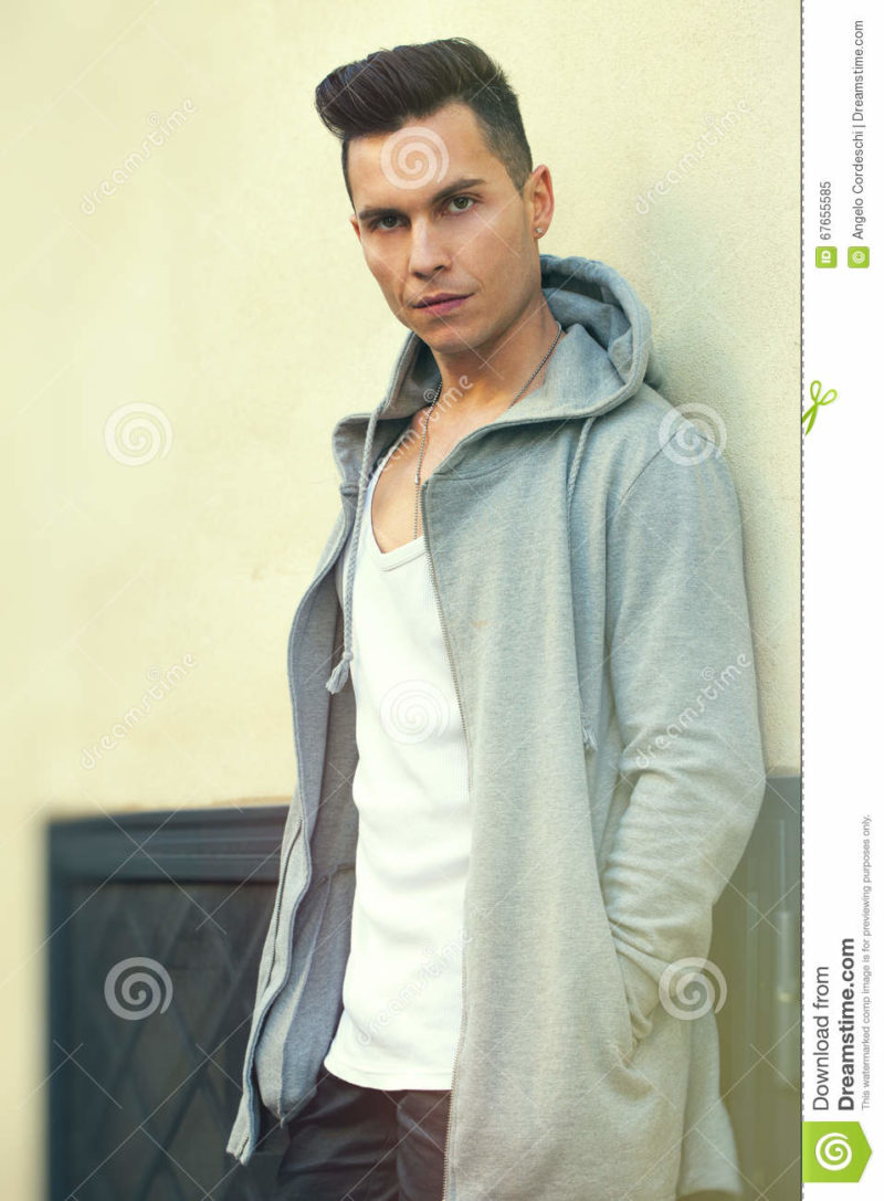 Portrait of serious young man leaning against the wall. Fashion hair style A young man dressed in youth fashion. He is leaning against a wall and stares intently. Hands in the pockets of the long hooded sweatshirt.