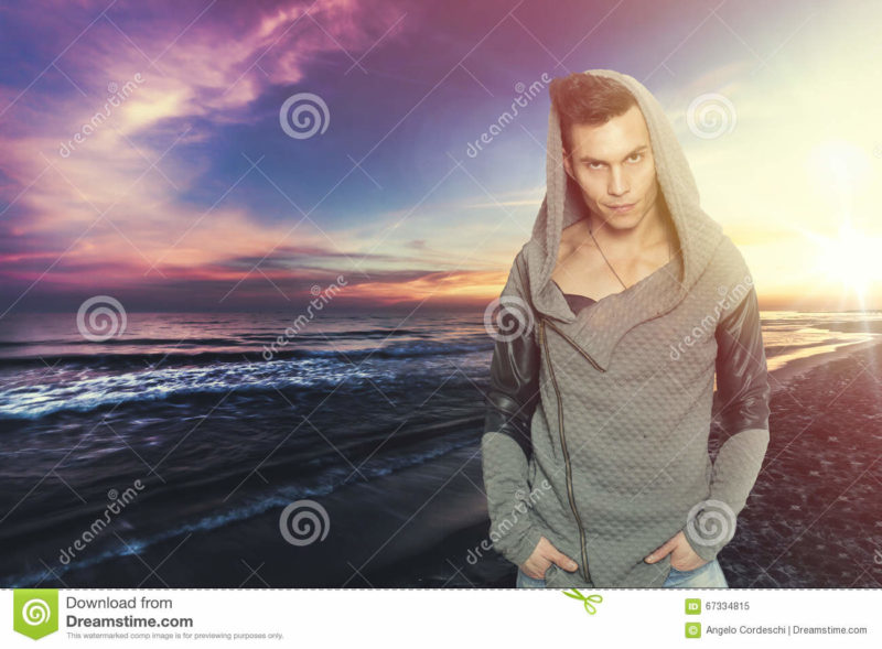 Stylish man with hooded sweatshirt the sea. Colorful sunset Stylish man with hooded sweatshirt the sea. Colorful sunset. A young man with attitude between grumpy and confidant. fashionable clothes, hooded sweatshirt. Beautiful landscape of the sea with sunset behind him.