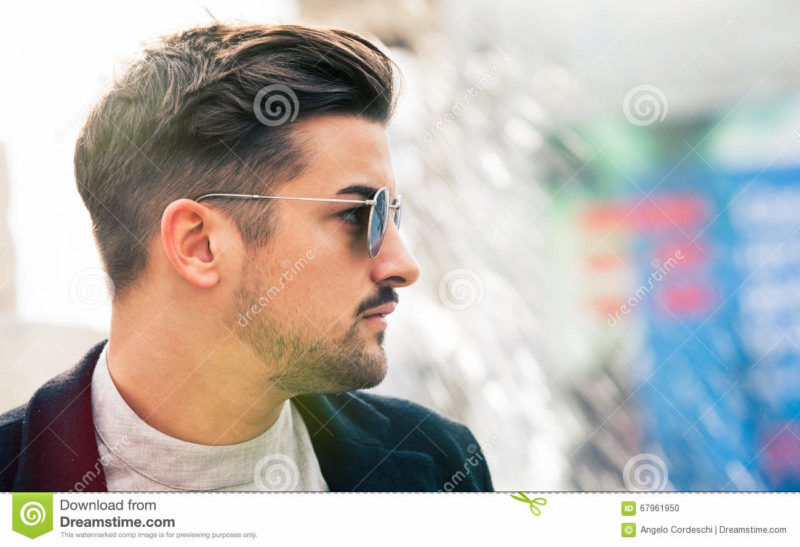 Stylish straight hair. Man profile with sunglasses. A handsome young man wearing sunglasses. Close portrait with face in profile. Space on the right for insertion of text or custom graphics. Youth trendy fashion concept. Outdoors