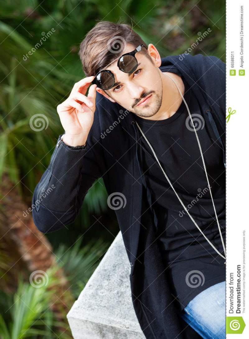 Sunglasses. Young gorgeous young man. A young handsome man discovering his eyes moving up sunglasses. Dresses the youth fashion. Chain around his neck. Outdoors.