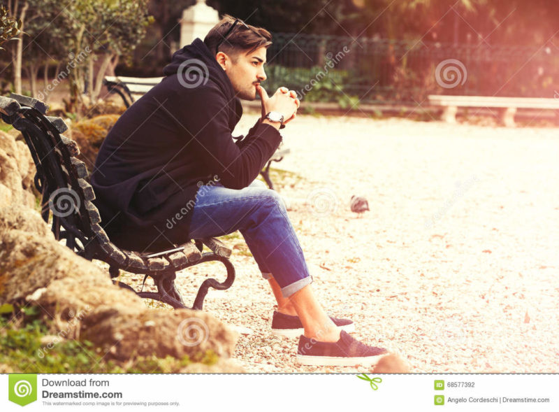 Thinking, thoughtful handsome man on the bench. Outdoors Young and handsome Italian man outdoors in a natural park in Rome, Italy. The boy is thoughtful and is thinking relaxed. Modern contemporary clothing. Trousers with turn-ups. Light warm sunbeam