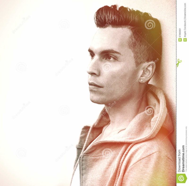 Vintage portrait. Young man model hairstyle looking A handsome man is relaxed with his back to a wall. vintage retro colors. His gaze is serious and serene, he is thinking. The hair of the young man are fashionable. Helpful copyspace.