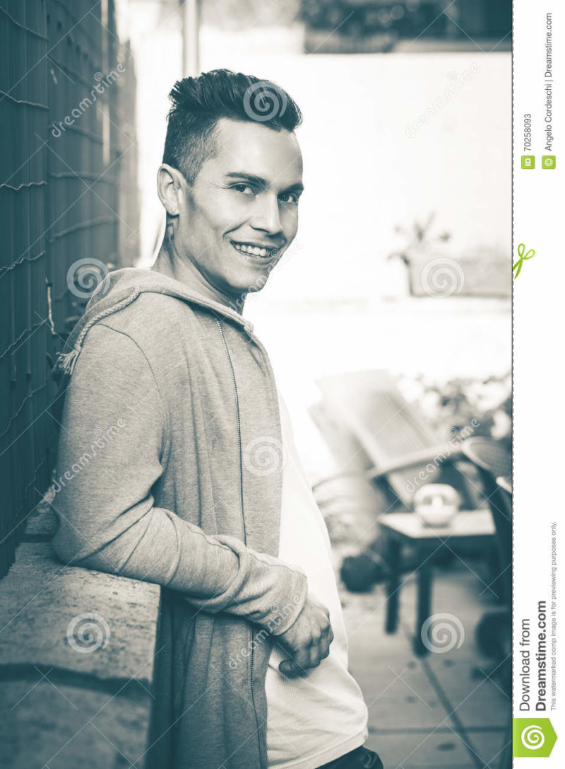 Vintage portrait. Young smiling man model hairstyle looking A handsome man is relaxed with his back to a low wall. Vintage retro colors. His gaze is happy and serene. The hair of the young man are fashionable.