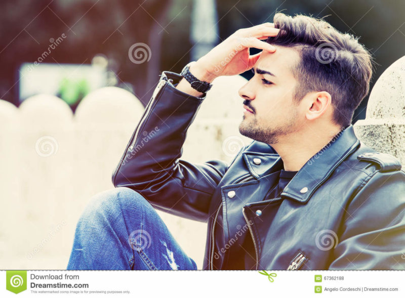 Worried young man, concern concept. Outdoor A young, beautiful and modern man is sitting with his forehead. He is thoughtful and slightly worried. Outdoors in a park, the young man has a stylish hair cut.