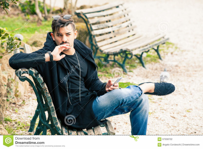 Young man sitting on the bench thinking waiting with phone in hand A handsome young boy sitting outdoors on a bench in a nature park in the city center. The young man wearing fashionable clothes youth. Waiting concept, doubts, misgivings, falling in love, social. Location: Rome, Italy.