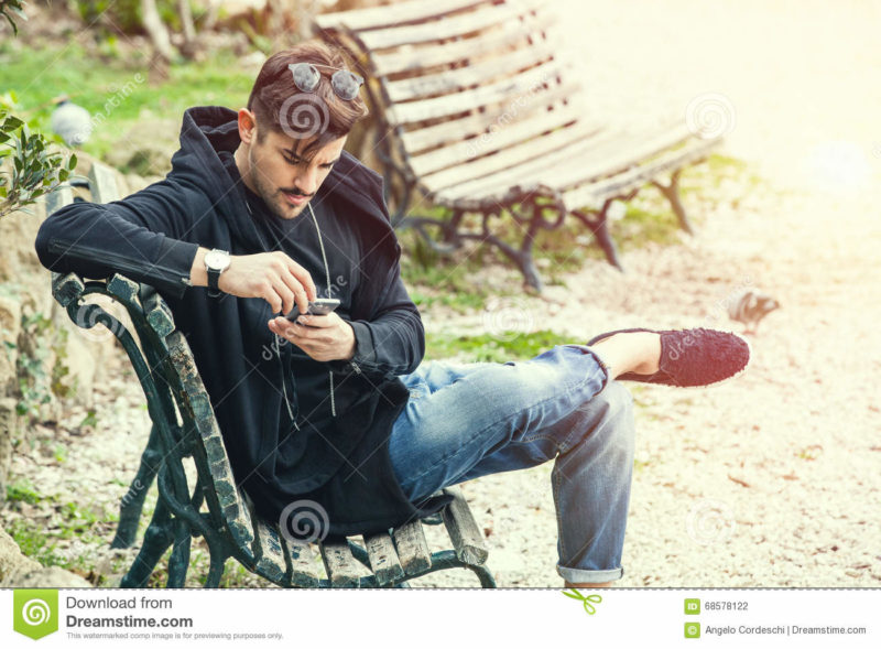 Young man sitting on the bench waiting with phone in hand A handsome young boy sitting outdoors on a bench in a nature park in the city center. The young man wearing fashionable clothes youth. Waiting concept, doubts, misgivings, falling in love, social. Location: Rome, Italy.