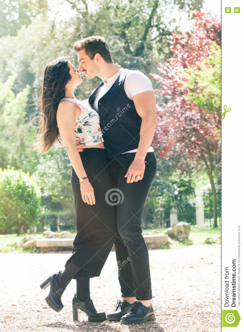 Beautiful couple embrace and love. Loving relationship and feeling. A men and a women is strongly embrace with passion and feeling. Love affair between two young people. Behind them a natural park with trees and colorful foliage. Bright light that illuminates the scene.