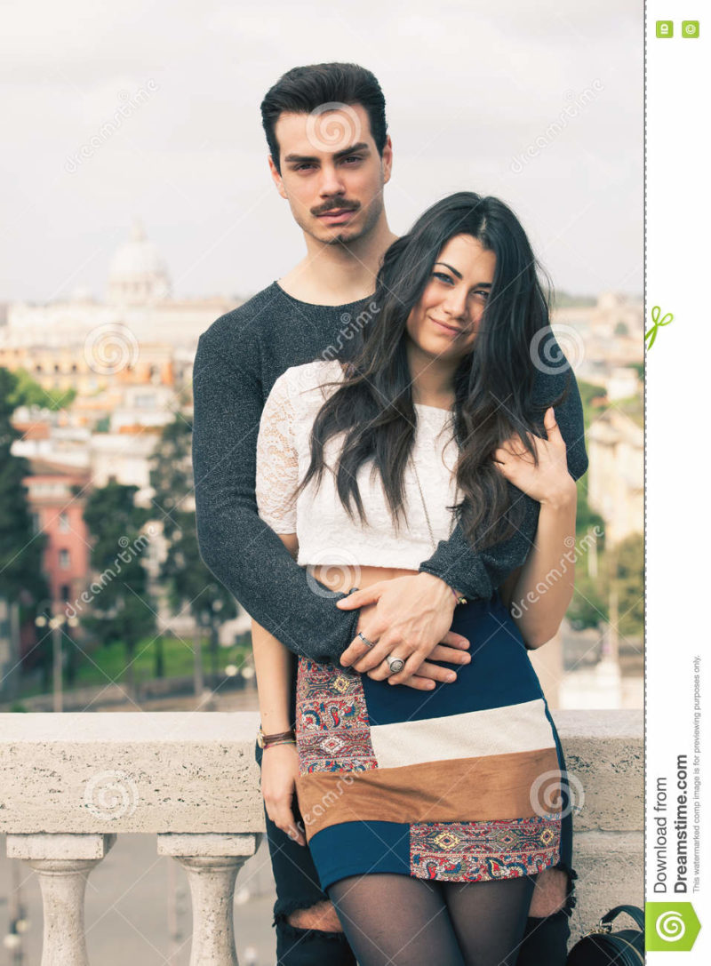 Beautiful embracing lovely young italian couple outdoors A couple, young men and a women outdoors, is embracing on a terrace in the historic center of Rome, Italy. Black hair. Bright daylight. The men has a mustache. Fashionable youth clothes.