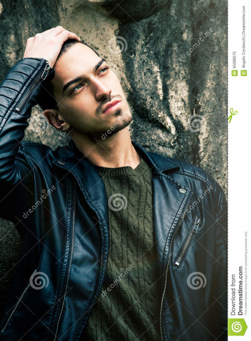 Beautiful young cool man with hand on head A cool guy posing outdoors with his hand on his head. Fashion rock style with leather jacket. Intense gaze.