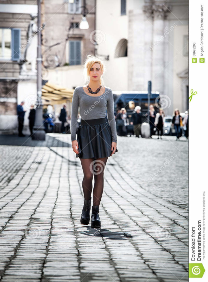 Blonde girl walking on the street in the city wearing a skirt. Girl walking on the street in the city. Beautiful young girl walking in the historic center of Rome, Italy. Driveway with paving of cobblestones. Wearing a skirt