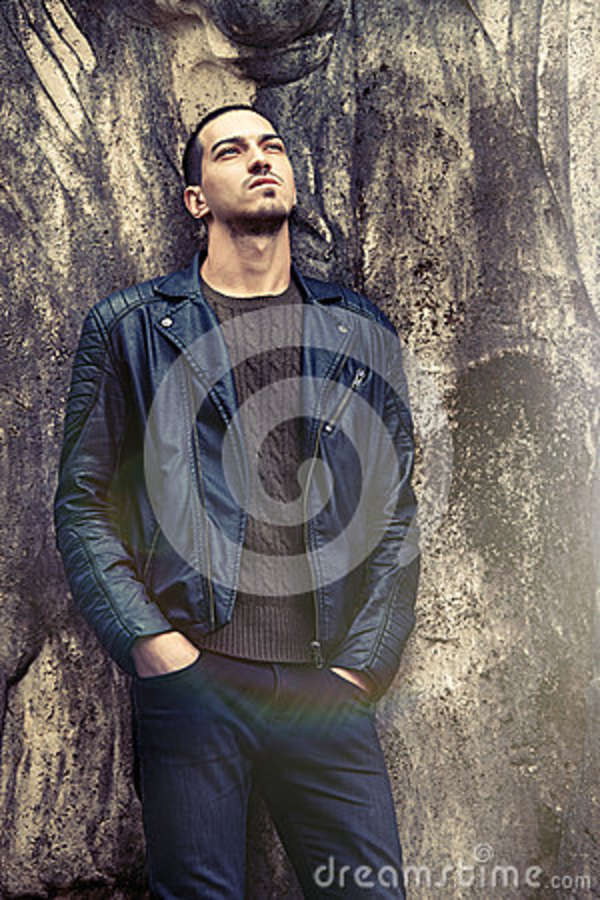 Cool trendy man leaning against the wall. Rock style clothing A handsome boy is posing with his back to a grunge concrete wall. Charming environment. Clothing rock fashion style with leather jacket.