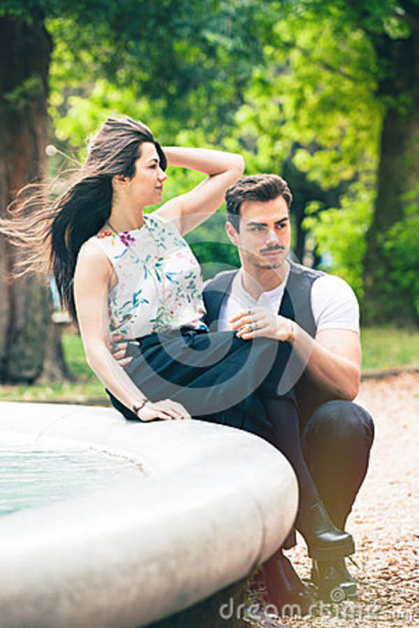 Couple outdoors romance lovers in a park. Loving romantic relationship. A beautiful young couple is relaxing in a park with trees and vegetation. The girl is sitting on a fountain. The young men crouched in front of her. Hair in the wind.
