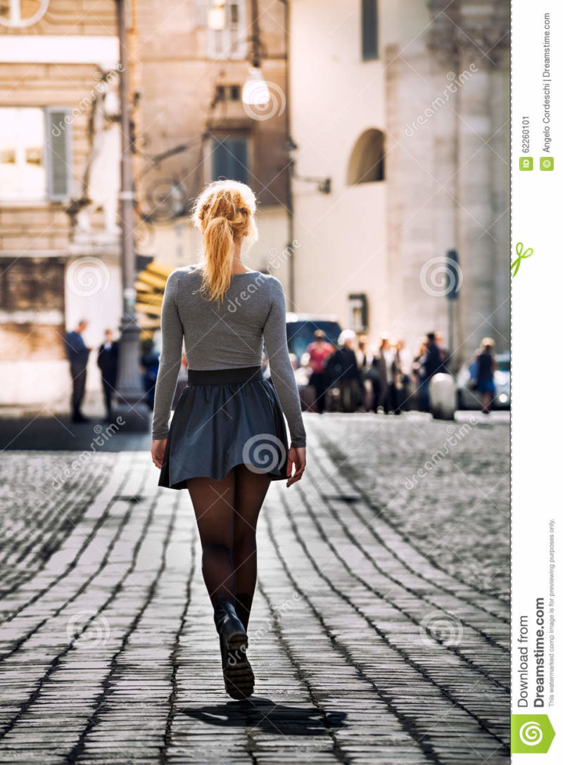 Girl walking on the street in the city wearing a skirt. Back. Girl walking on the street in the city. Back. Beautiful young girl walking in the historic center of Rome, Italy. Driveway with paving of cobblestones. Wearing a skirt