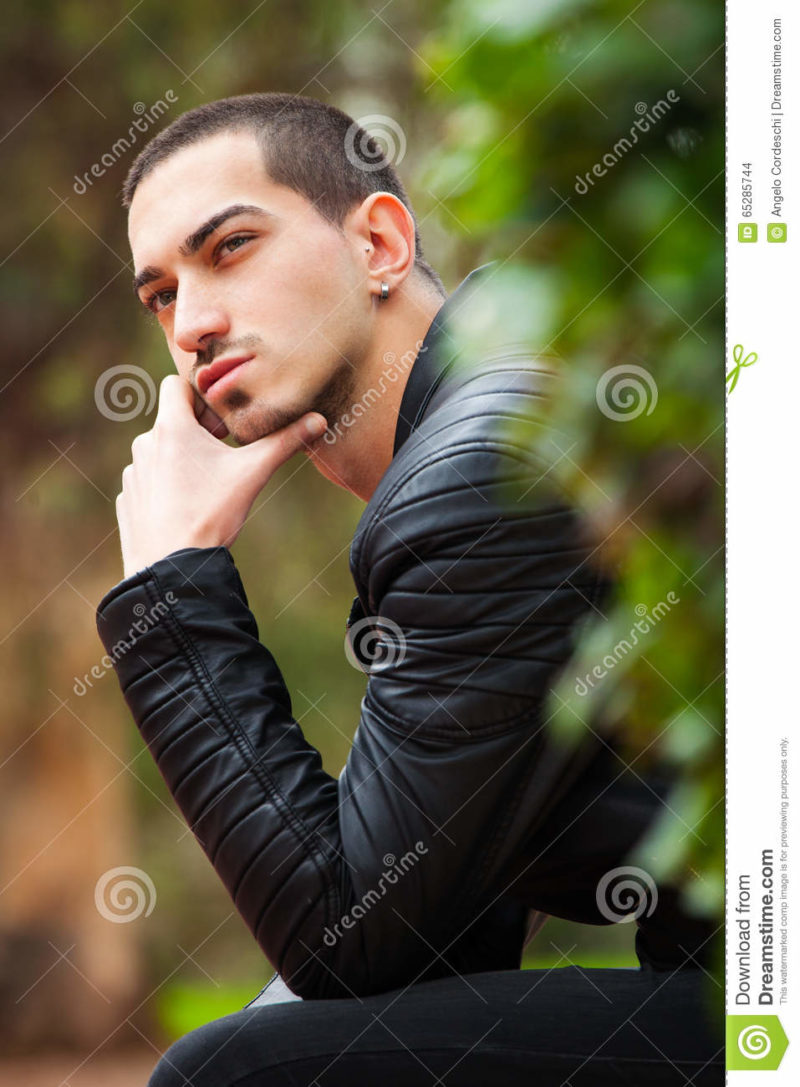 Handsome guy sitting thinking. Short hair A thoughtful handsome man has a hand under his chin and thinking. Outdoors in a park sitting on a bench, a hedge hides part of his body. Italian male