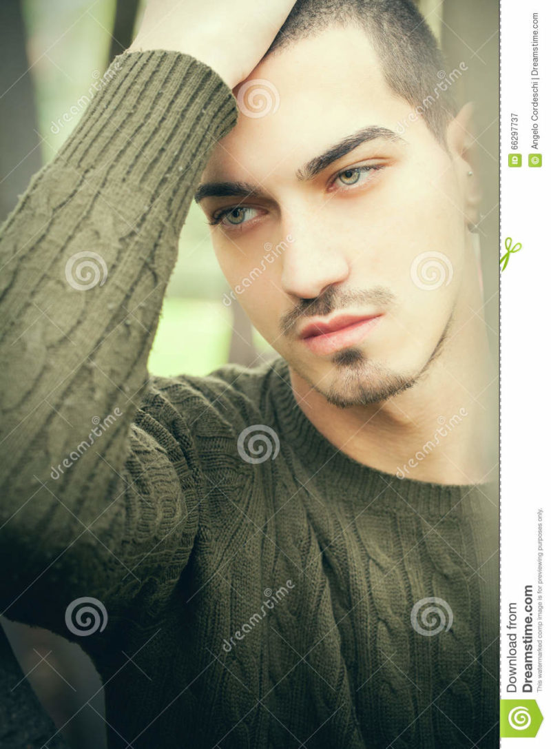 Handsome man green eyes and short hair Close portrait of a beautiful, attractive and charming young boy. He has short hair and light eyes. Harmony and serene scene.