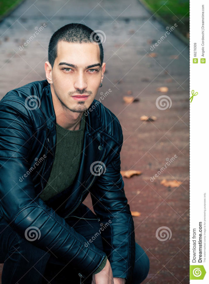Handsome man short hair style outdoors Handsome young model outdoors. Intense look, leather jacket. Light eyes. Road with autumn scene behind him. Some leaves on the ground. Short hair style.