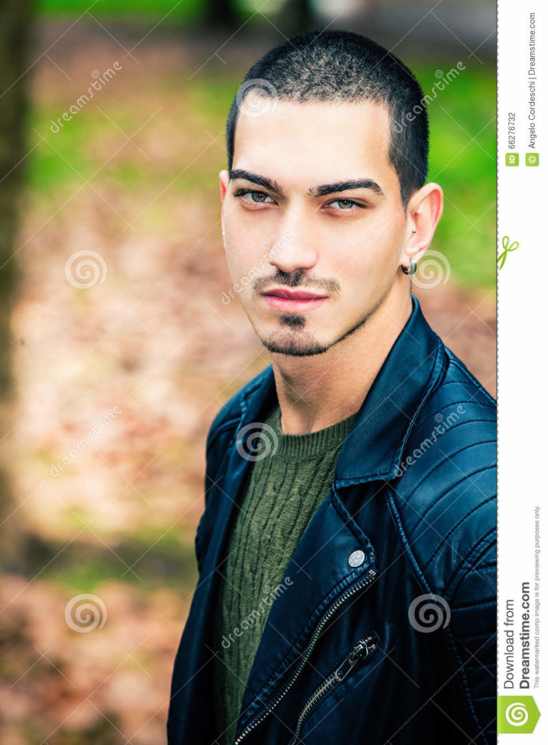 Handsome young man outdoors, short hair style A handsome boy outdoors. Eyes with intense look and stylish hair. Behind him one winter autumn scenery. The young man wearing a leather jacket rock style.