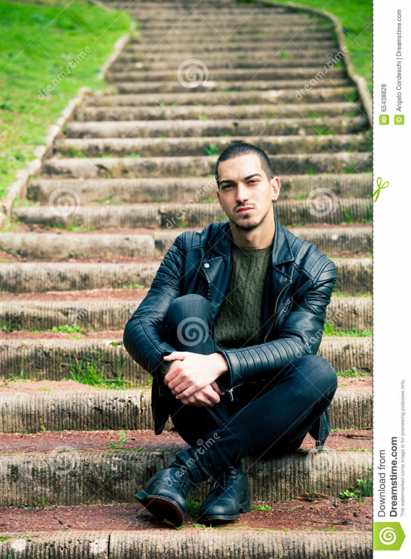 Handsome young man sitting on steps outdoors. Handsome young boy sitting on a staircase in a natural park. Crouch, rock style clothes with leather jacket and dark jeans. Short hair and earring.