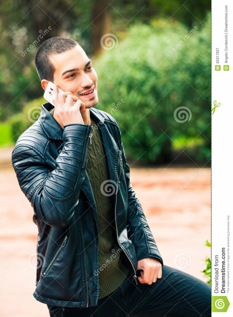 Happy young man with smartphone. Talking on the phone. Telephone conversation. Happy man outdoor. A young and handsome boy is talking on the phone with someone. His mood is positive. Outdoors in a park.