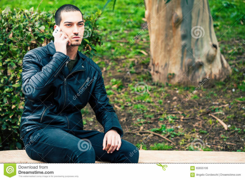 Happy young man with smartphone. Talking on the phone. Telephone conversation. Happy man outdoor. A young and handsome boy is talking on the phone with someone. His mood is serious. Outdoors in a park.