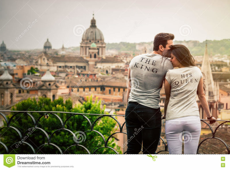 The king, his queen. Romantic couple in Rome, Italy. Two young people, a men and a women are kissing and loving. On a terrace with railing overlooking Rome, the Italian capital in Italy. The two beautiful young wearing a gray T-shirt with the words The King and His Queen. Monuments and churches with a dome on romantic background.