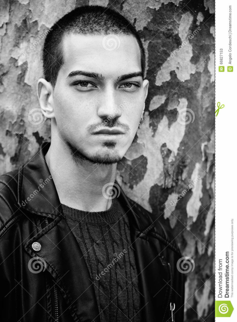 Man portrait outdoors. Handsome natural male. Black and white Portrait of a young handsome man near a tree. Intense gaze and eye-catching. Italian man. Tree with camouflage texture as background. Black and white
